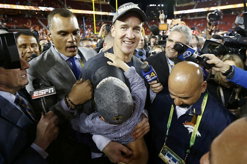 Denver Broncos' quarterback Peyton Manning carrying his son as he walks off the field after the Broncos defeated the Carolina Panthers on Feb 7, 2016.