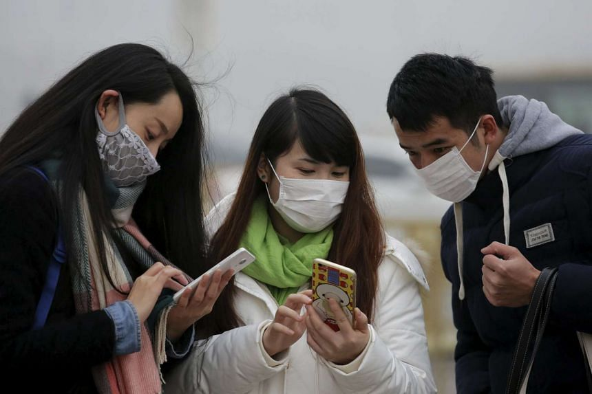 People wearing protective masks checking their phones at the Tiananmen Gate on Dec 1, 2015.