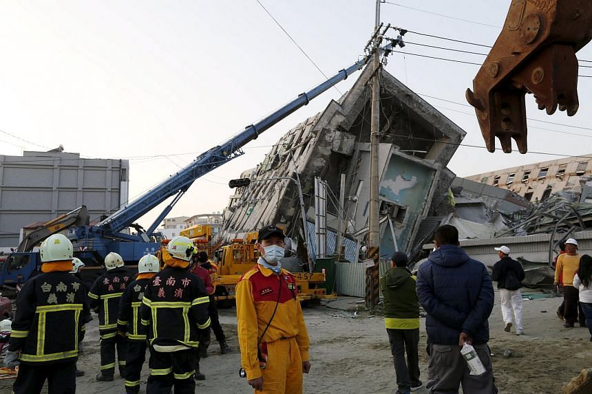 Rescue workers standing in front of the building which collapsed after an earthquake hit Tainan,  Taiwan on Feb 7, 2016.