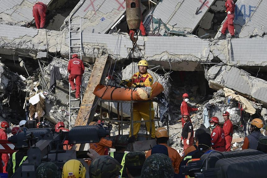 A rescue worker bringing down a victim from the collapsed building in Tainan, Taiwan.