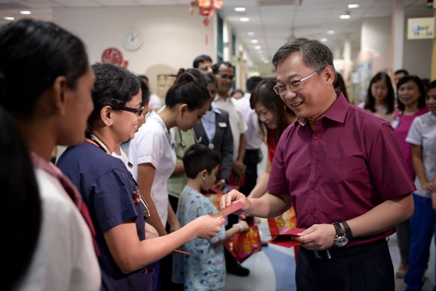 Health Minister Gan Kim Yong greeting National University Hospital (NUH) staff during a visit with his wife on Feb 8, 2016.