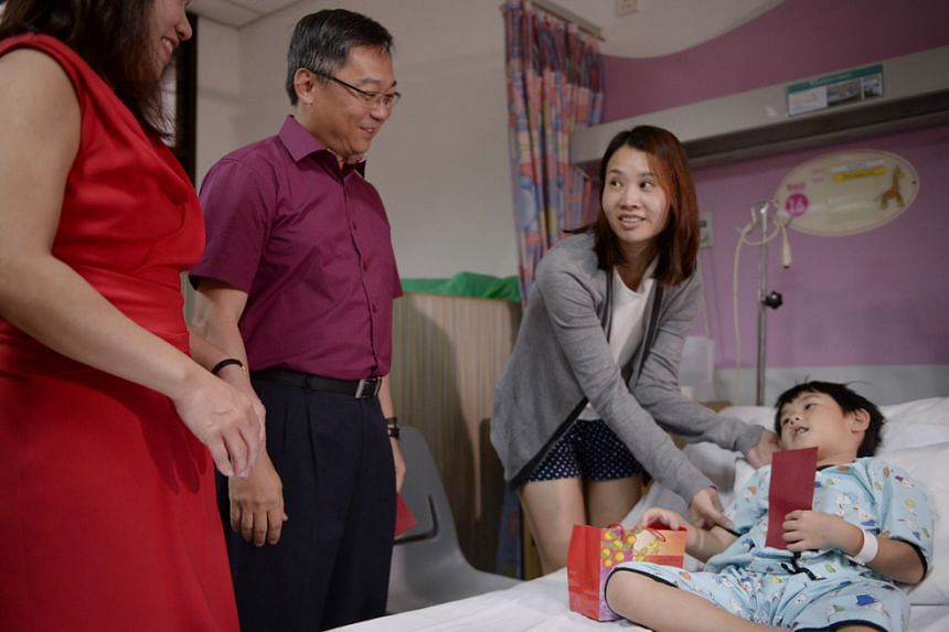 Health Minister Gan Kim Yong (second from left) and his wife (far left) passing angbaos and oranges to Krislyn Chia, 39, and her son Aiden Han, six, who was warded for a toe infection at NUH on Feb 8, 2016.