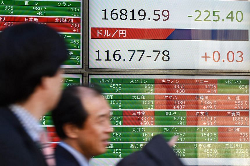 Businessmen walking past an electric quotation board flashing the Nikkei key index of the Tokyo Stock Exchange in front of a securities company in Tokyo on Feb 5, 2016.