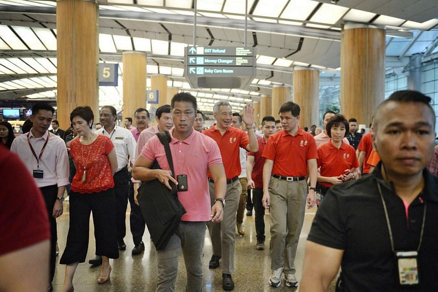 PM Lee Hsien Loong waving to people during a visit to Changi Airport Terminal 2 with union leaders on Feb 8, 2016.