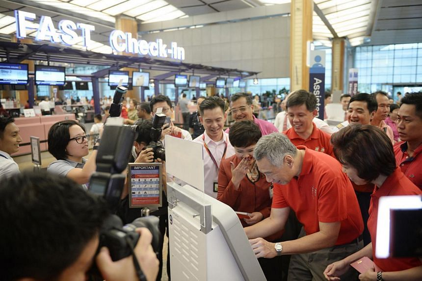 PM Lee Hsien Loong trying out a machine at the FAST Check-in Counter accompanied by SATS Customer Service Officer Rita Ahmad, 42, during a visit to Changi Airport Terminal 2 with union leaders on Feb 8, 2016.