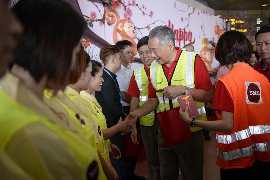 PM Lee Hsien Loong greeting SATS staff at Changi Airport Terminal 2 on Feb 8, 2016.