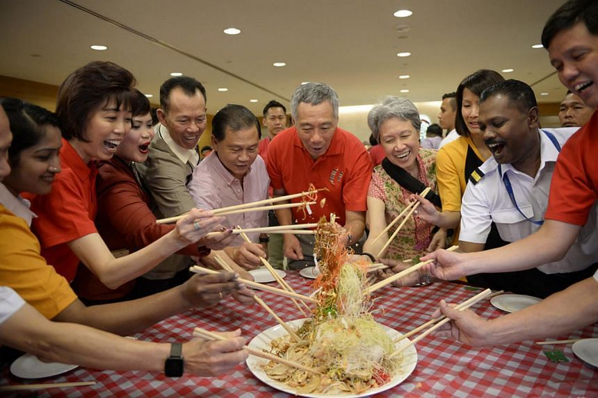 PM Lee Hsien Loong and his wife Ho Ching, along with union leaders and several airport staff tossing the traditional Lo Hei at Changi Airport Terminal 2 on Feb 8, 2016.