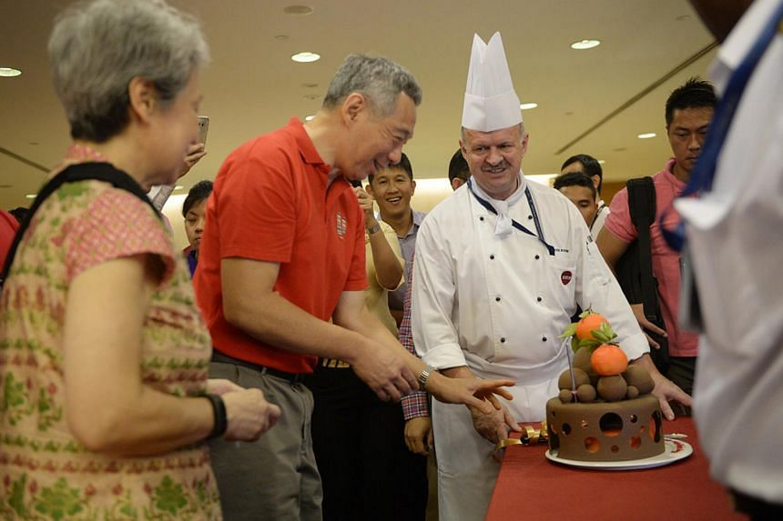 PM Lee Hsien Loong reacting after getting surprised with a birthday cake during a visit to Changi Airport Terminal 2 on Feb 8, 2016.