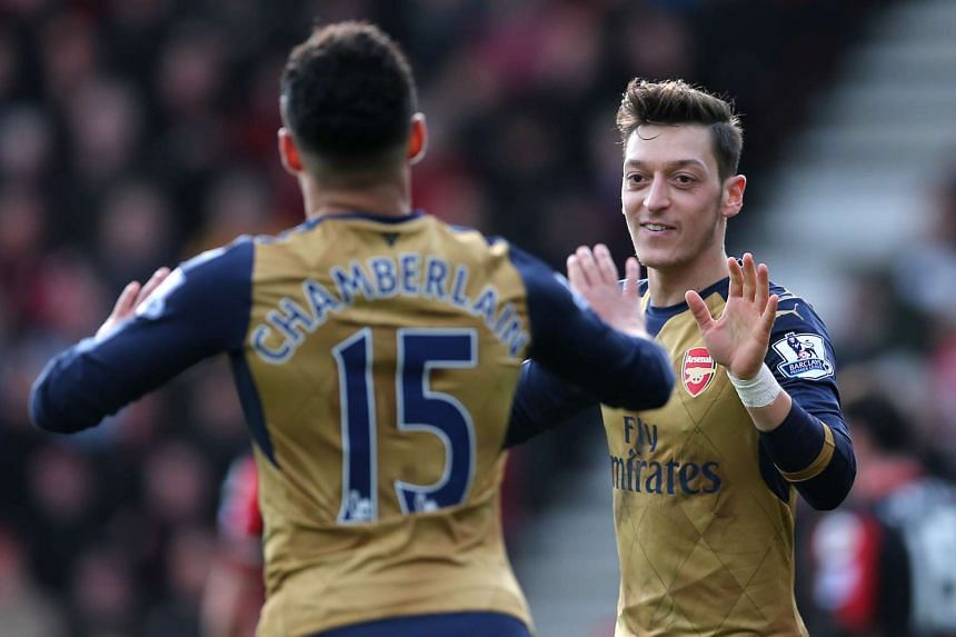 Mesut Ozil celebrates with Alex Oxlade Chamberlain after scoring the first goal for Arsenal against Bournemouth on Sunday.