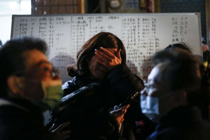 A relative reacts as rescuers search for survivors on the eve of Chinese New Year from a collapsed building following the earthquake that struck Tainan City.