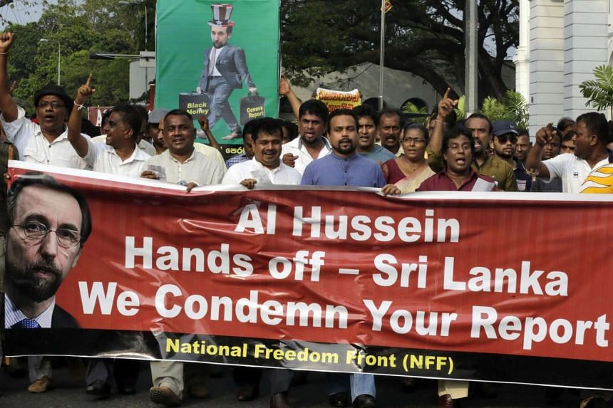 Protestors from the National Freedom Front hold hold posters criticising the visit of United Nations Prince Zeid Ra'ad Zeid Al-Hussein, outside the UN office in Colombo.