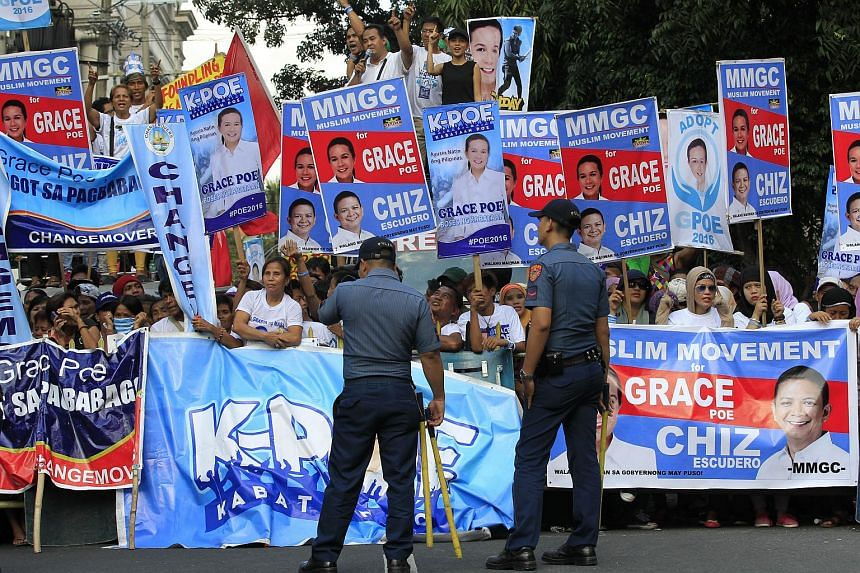 Anti-riot policemen standing guard in front of the supporters of Philippines' Senator and presidential candidate Grace Poe.