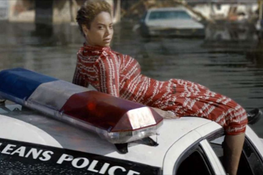 Beyonce in the music video, Formation, on top of a sinking police car.