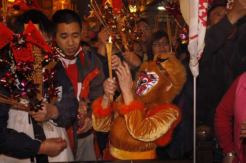 A worshipper dressed as a monkey making her first offering inside Wong Tai Sin Temple, in Hong Kong, China on Feb 7, 2016.