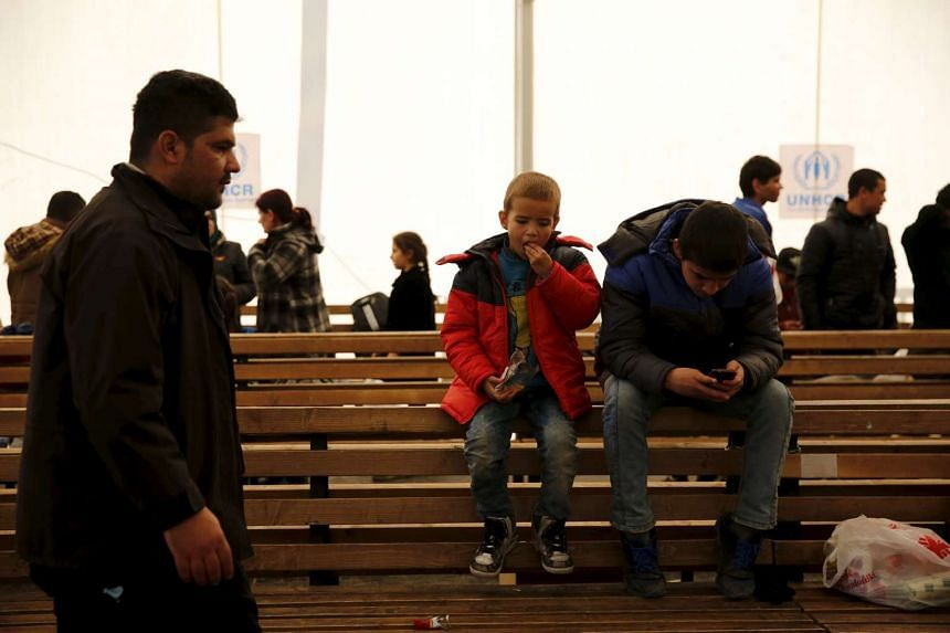Children sit on a bench as refugees and migrants wait for a train to continue their journey towards western Europe from the Macedonia-Greece border at the Vinojug Temporary Transit Centre on Feb 1, 2016.