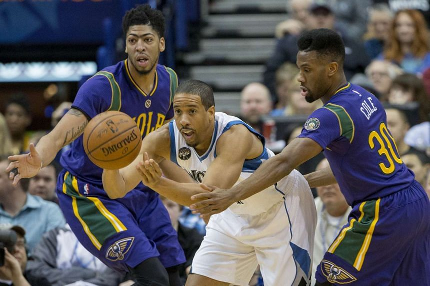 Minnesota Timberwolves guard Andre Miller (centre) passes the ball between New Orleans Pelicans' Anthony Davis (left) and Norris Cole.