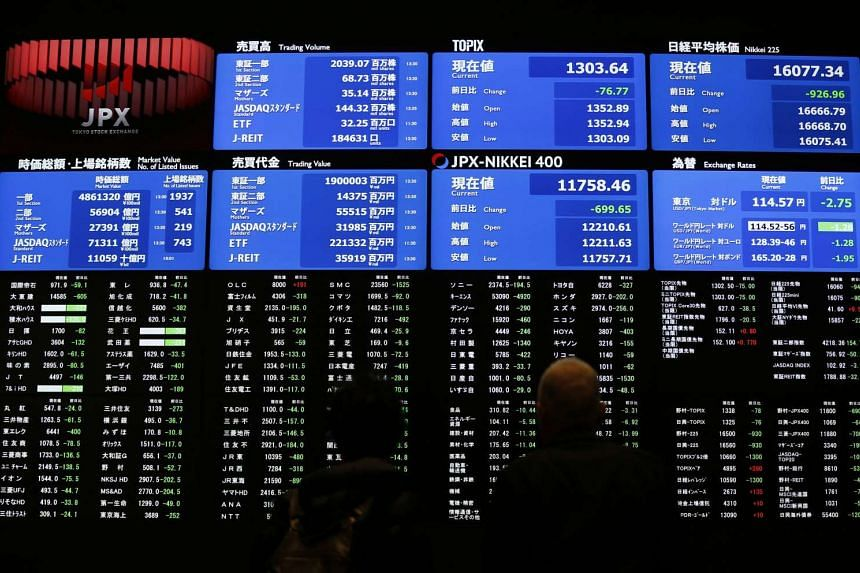 Visitors look at an electronic board showing Japan's Nikkei average at the Tokyo Stock Exchange on Feb 9, 2016.