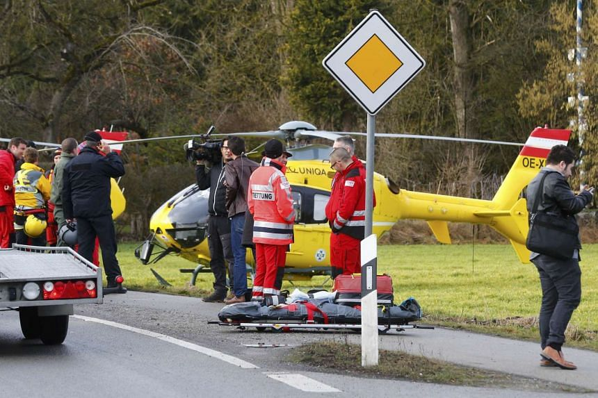 Rescuers and journalists stand in front of a rescue helicopter near Bad Aibling in southwestern Germany on Feb 9, 2016.