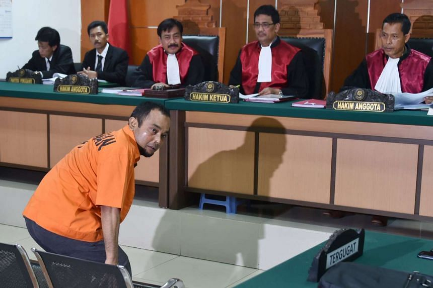 Suspected Islamic radical identified as Aprimul looks back to journalists during his court appearance in Jakarta on Feb 9, 2016.
