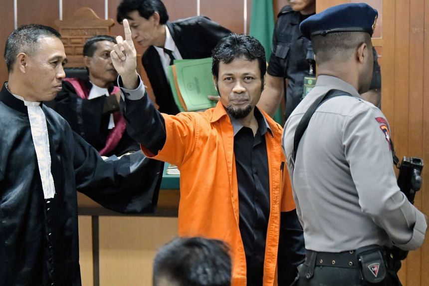 Suspected Islamic radical identified as Muhammad Fachry (centre) gestures at his court appearance in Jakarta on Feb  9, 2016.