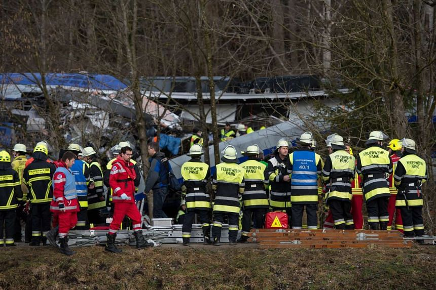 Rescue teams work at the site of a train accident near Bad Aibling, Germany, on Feb 9. At least four people are dead and another 150 injured after two commuter trains collided head on near the southern German town of Bad Aibling, police said.
