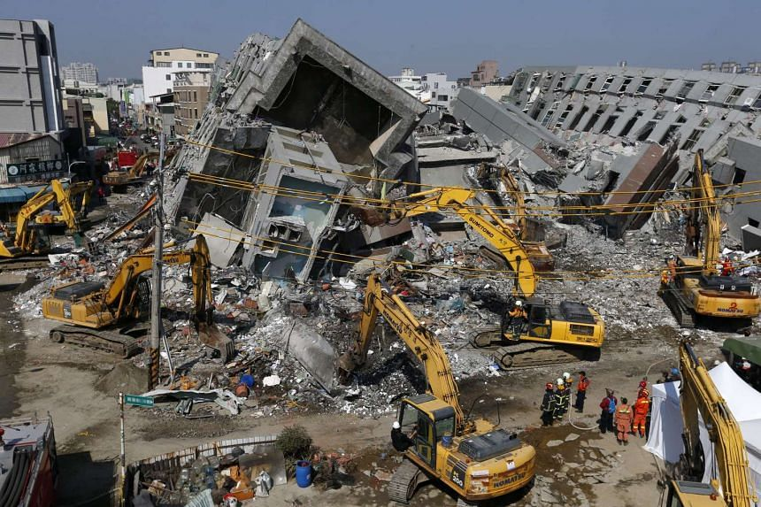 Rescuers use heavy equipment to knock down parts of a collapsed 17-storey apartment building in Tainan, Taiwan on Feb 9, 2016.