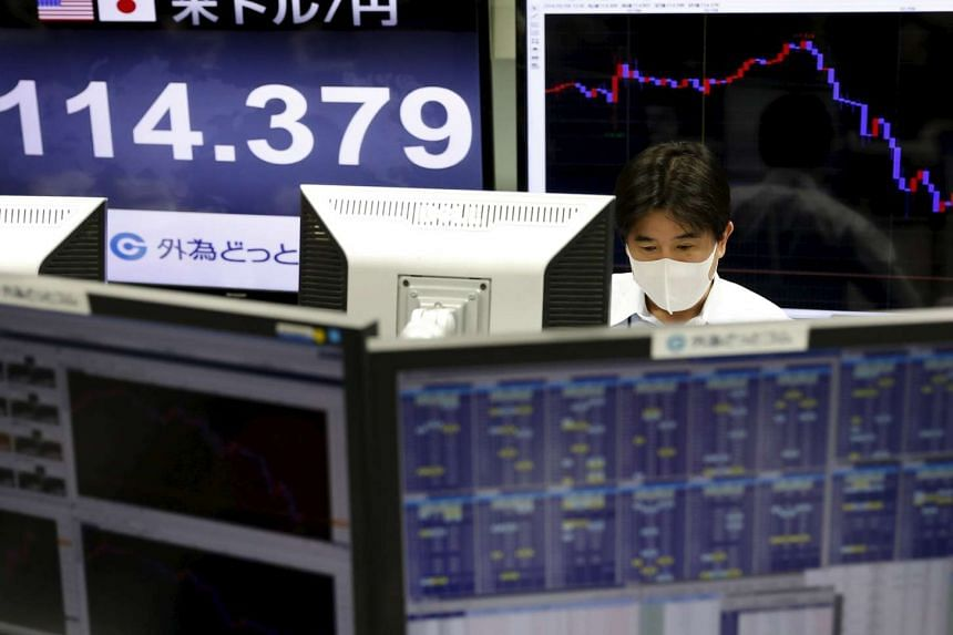 An employee of a foreign exchange trading company working in front of monitors displaying the Japanese yen's exchange rate against the US dollar in Tokyo, Japan, on Feb 9, 2016.