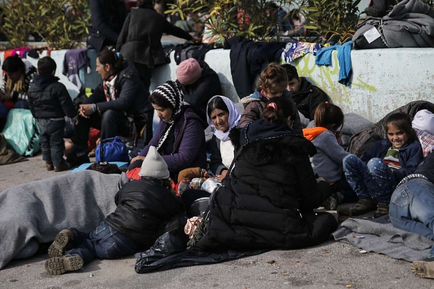 Refugees and migrants resting outside a passenger terminal at the port of Piraeus, near Athens, Greece, on Feb 8, 2016.