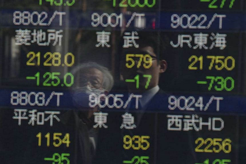 People look at an electric quotation board of the Tokyo Stock Exchange in Tokyo on Feb 9, 2016.