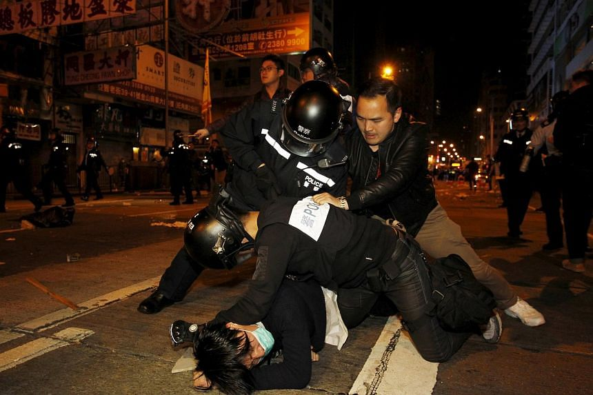 A protester (bottom) is arrested by riot police during a clash at Hong Kong's Mongkok shopping district, China early on Feb 9, 2016.