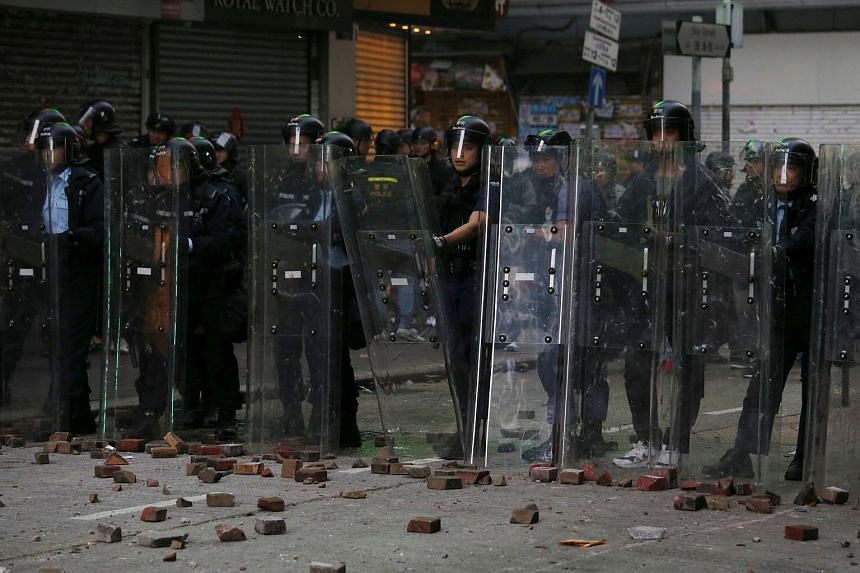 Stones thrown by protesters are seen on the ground in front of the riot police during a clash at Mongkok district in Hong Kong, China on Feb 9, 2016.