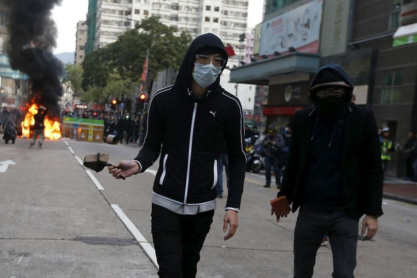 Protesters preparing to throw stones towards the riot police after starting a fire at a junction in Mongkok district in Hong Kong, China on Feb 9, 2016.