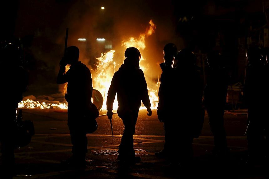 A riot policeman walking in front of a fire set by protesters at a junction in Mongkok district in Hong Kong, China on Feb 9, 2016.