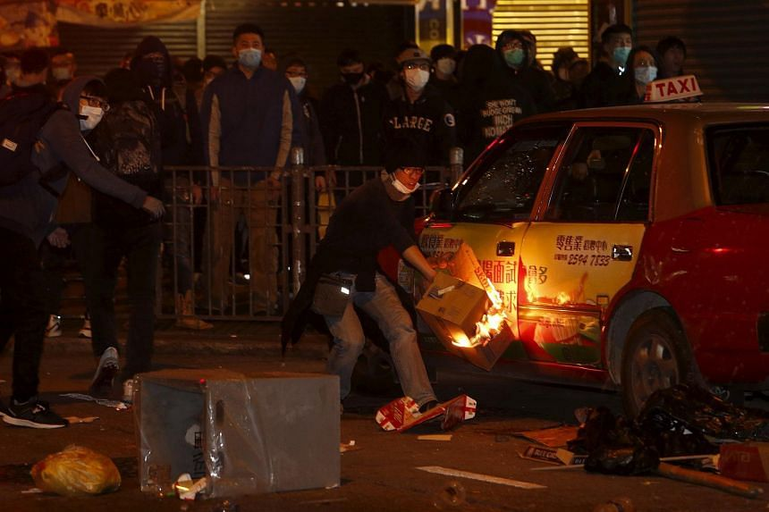 A protester starting a fire beside a parked taxi at Mongkok district in Hong Kong, China on Feb 9, 2016.
