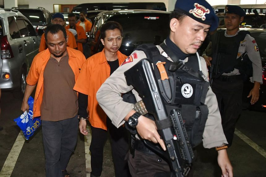 Indonesian armed police escort suspected Islamic radicals to court in Jakarta on Feb 9, 2016.