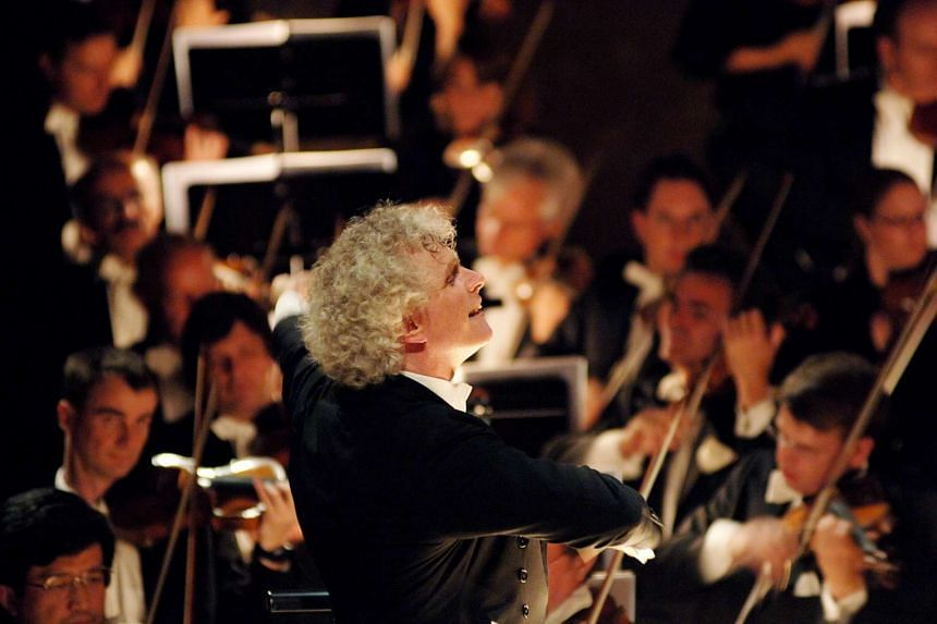 Sir Simon Rattle conducting the Berlin Philharmonic orchestra in a file photo.