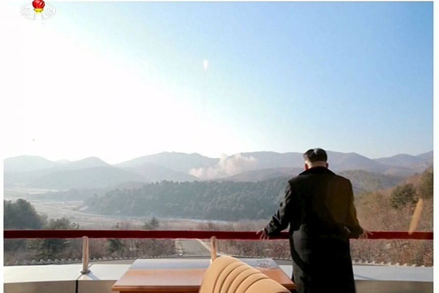 North Korean leader Kim Jong Un watching a long range rocket launched into the air.