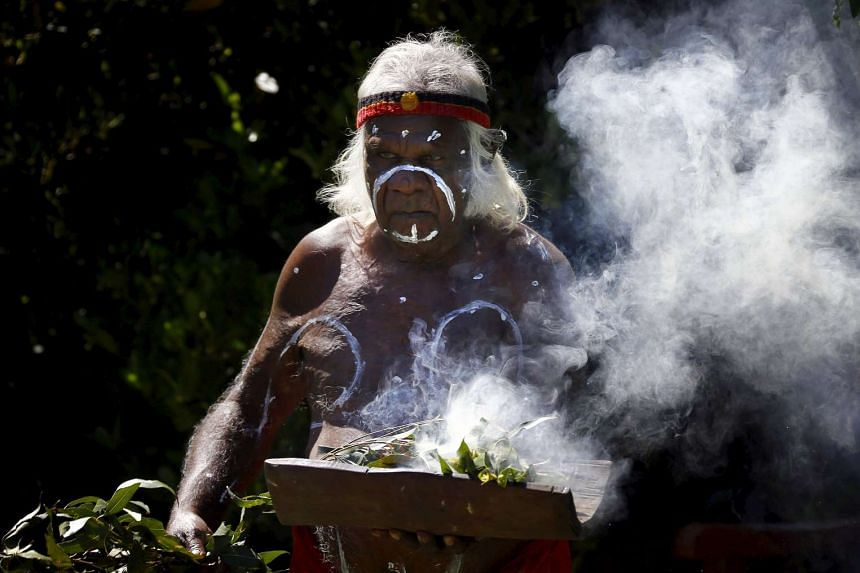 Aboriginal elder Max Eulo performs a smoking ceremony on the foreshore of Sydney Harbour on Nov 27, 2013.