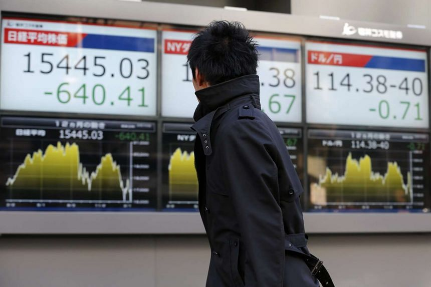 cap: A businessman looking at boards displaying Tokyo's Nikkei Stock Average (left) in Tokyo, Japan, on Feb 10, 2016.