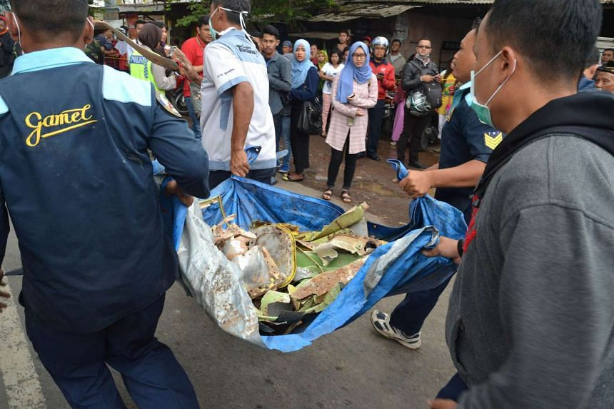 Indonesian officials carrying pieces of wreckage from a military plane after it crashed in a densely populated area in Malang, East Java, on Feb 10, 2016.