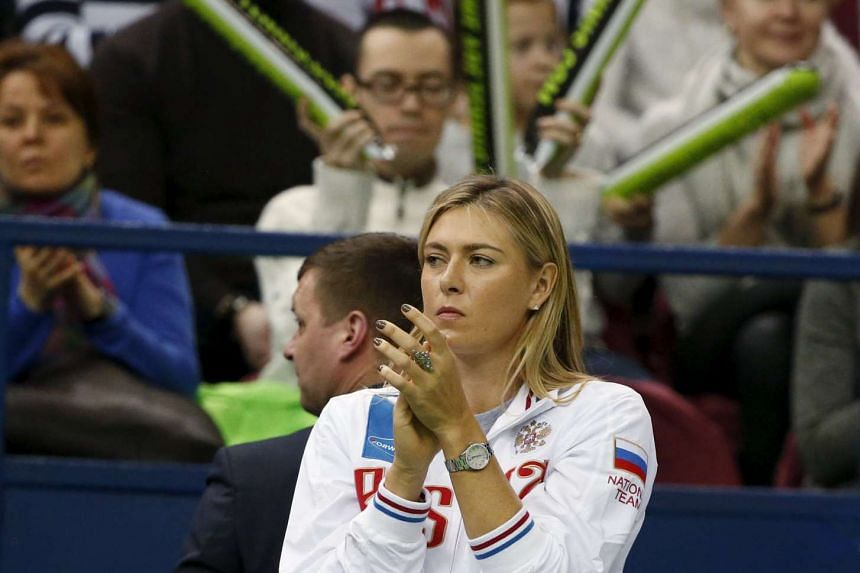 Maria Sharapova reacts as she watches Ekaterina Makarova play against Kiki Bertens of the Netherlands during the Fed Cup.