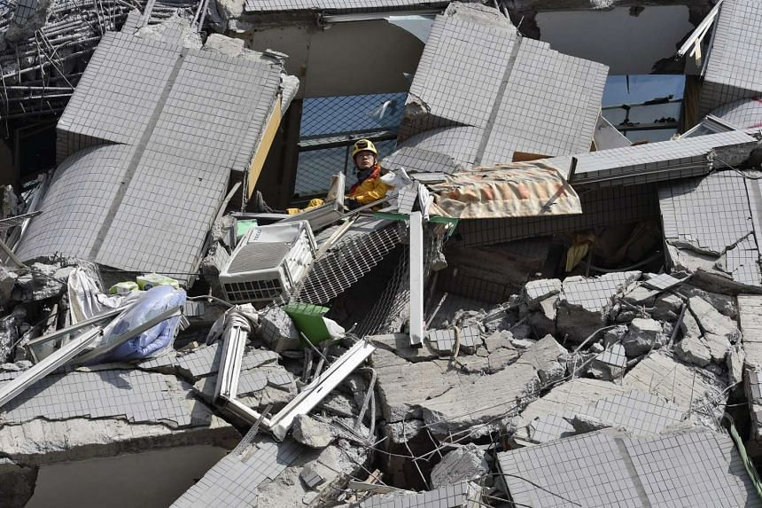 A rescuer waits for a crane at the collapsed Wei Kuan complex building on the second day of rescue operations.