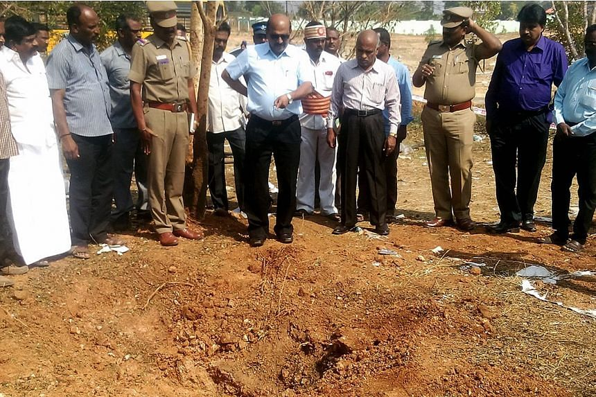 Indian authorities inspect the site of the suspected meteorite landing on Feb 7, 2016 that killed a bus driver and injured three others in an impact on Feb 6.