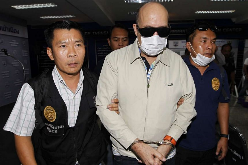 Hamid Reza Jafary (centre), a suspect involved in supplying fake passports at the Immigration Bureau in Bangkok on Feb 9, 2016.