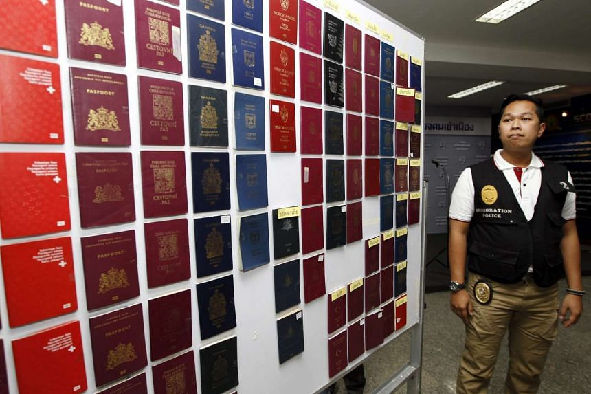 A Thai immigration policeman stands next to fake passports at the Immigration Bureau in Bangkok on Feb 9, 2016.