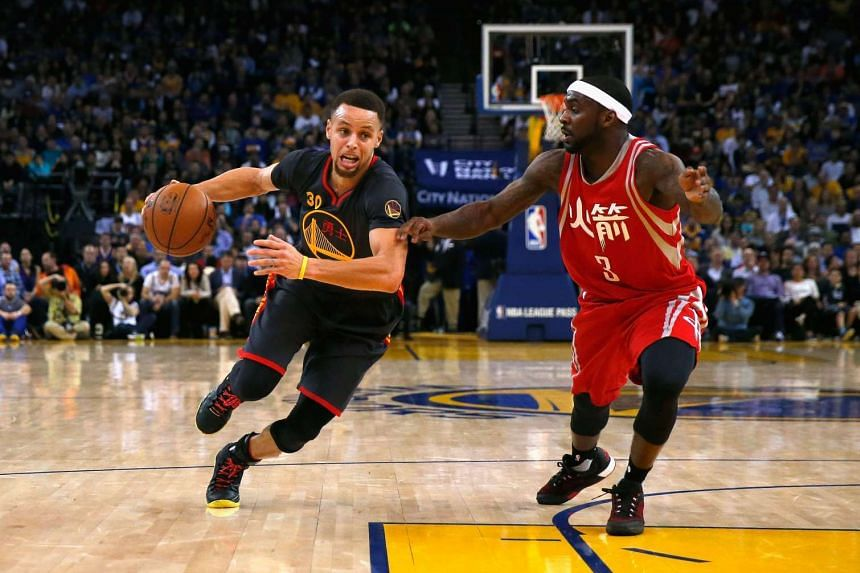 Stephen Curry of the Golden State Warriors drives on Ty Lawson of the Houston Rockets.