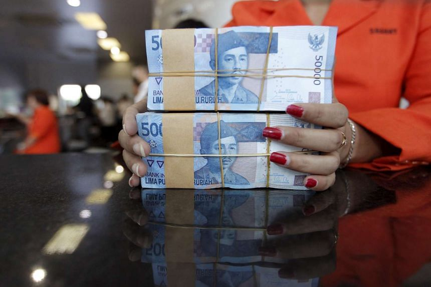 A teller prepares rupiah notes for a customer at a money changer in Jakarta.