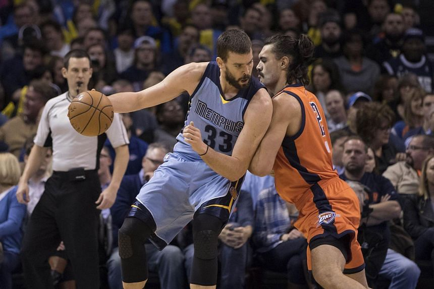 Steven Adams #12 (right) of the Oklahoma City Thunder applies pressure as Marc Gasol #33 of the Memphis Grizzlie looks for a play.