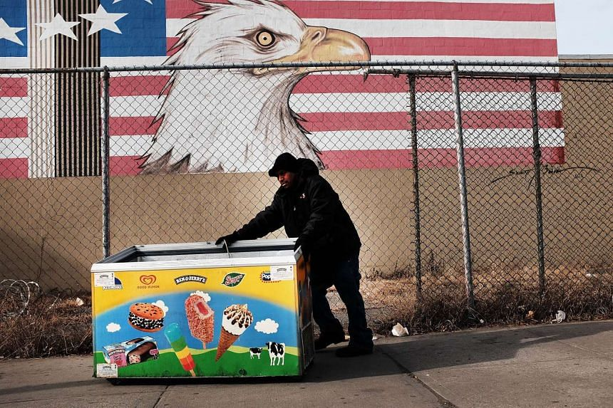 A man pushes an ice cream freezer to a scrap metal yard in Brooklyn on Jan 8, 2016, in New York City.