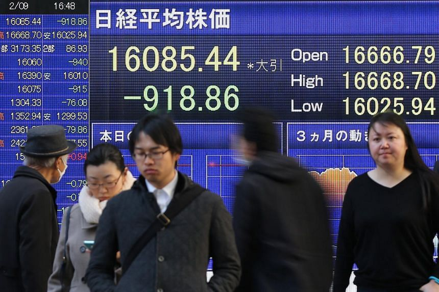 Pedestrians walk in front of a board displaying the closing price of the Nikkei 225 Stock Average in Tokyo, Japan, on Feb 9, 2016.